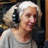 Une femme portant des écouteurs parle dans un micro.