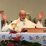 un curé donnant la messe, lève les mains en l'air en lisant la Bible.