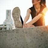 Une femme fait des étirements lors qu'une sortie de course à l'aube