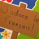 Une affiche faite par un enfant sur laquelle il est écrit : J'adore le français.
