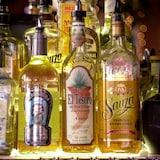 Des bouteilles de tequila sont placées côte à côte dans un bar de New York.