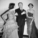 Le concepteur de mode Christian Dior avec deux mannequins portant ses créations.