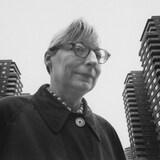 Jane Jacobs devant des tours d'habitation.