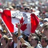 Un homme tient un drapeau du Canada dans une foule.