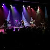 5 des 6 musiciens sont sur scènes devant des jeunes debout.