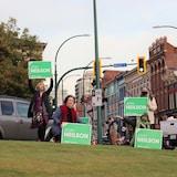 Jenn Neilson est entourée de son équipe et brandit une affiche verte avec son nom.