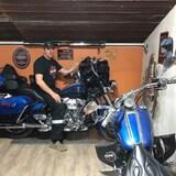 Joël Dillon est assis sur l'une de ses deux motos.