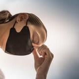Un femme la tête penchée portant un masque pendant la pandémie.