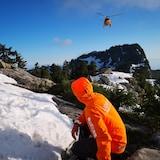 Un homme habillé d'une veste de sauvetage orange. Il est assis dans une montagne en neige et attend l'arrivée d'un hélicoptère