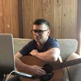Le chanteur de Vancouver, Loig Morin, assis devant son ordinateur avec une guitare pendant le confinement chez lui