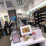 On aperçoit le magasin et les articles qui y sont en vente : chandelles, savons, cadres, décorations de maison, verres à vin, vêtements et bijoux.