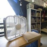 Un ventilateur est posé sur un bureau, devant une fenêtre.