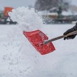 Une pelle soulève une bonne quantité de neige sur un grand terrain, à l'extérieur.
