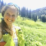 Maude Cyr sourit en pleine nature dans une vallée entre deux montagnes.