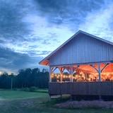 Un pavillon extérieur au milieu d'un champ où les gens se rencontrent pour une soirée dansante traditionnelle