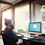 Une femme a son bébé dans les bras tandis qu'elle travaille sur un ordinateur.