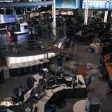 Une salle de rédaction avec des journalistes à leurs bureaux et un plateau de télévision.