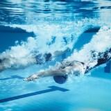 Deux nageurs font un départ sous l'eau les mains devant.
