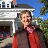 Nicole Guertin, devant une maison historique blanche.