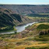 Une rivière coule entre des collines boisées.