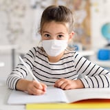 Trois élèves sont assises à des bureaux individuels dans une salle de classe et portent un masque.