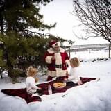 Dans un champ enneigé, le Père Noël fait un pique-nique. Il boit du lait et mange des biscuits avec deux fillettes.