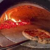 Une pizza ronde napolitaine transférer à l'intérieur d'un four de bois franc qui brule.
