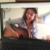 Caroline Allatt est a l'écran d'un ordinateur avec sa guitare.