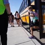 Une petite fille descend de l'autobus scolaire.