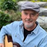 Le musicien Robert Walsh avec sa guitare dans un jardin.