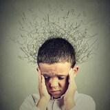 Un enfants se tient la tête entre les mains et a les yeux fermés