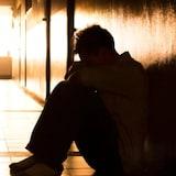 Un homme est recroquevillé dans un couloir sombre.