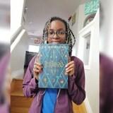 La jeune fille tient un livre dans une maison.