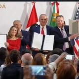 Les politiciens montrent leur signature respective sur le document.