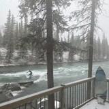 Un homme en combinaison fait du surf sur une rivière, l'hiver.