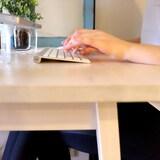 Les mains d'une femme sur un clavier d'ordinateur.