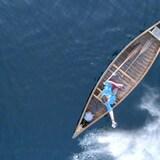 Une femme disperse des cendres dans l'eau depuis un bateau.