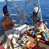 Laurent Torrecilles à la barre du voilier alors que Lynne et les enfants relaxent au soleil.