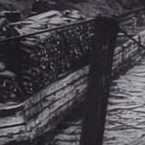 Un homme sur une barge flottant sur un lac.