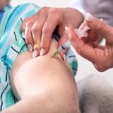 Une infirmière vaccine une personne âgée.