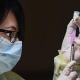Une travailleuse de la santé remplit une seringue du vaccin de Pfizer-BioNTech.