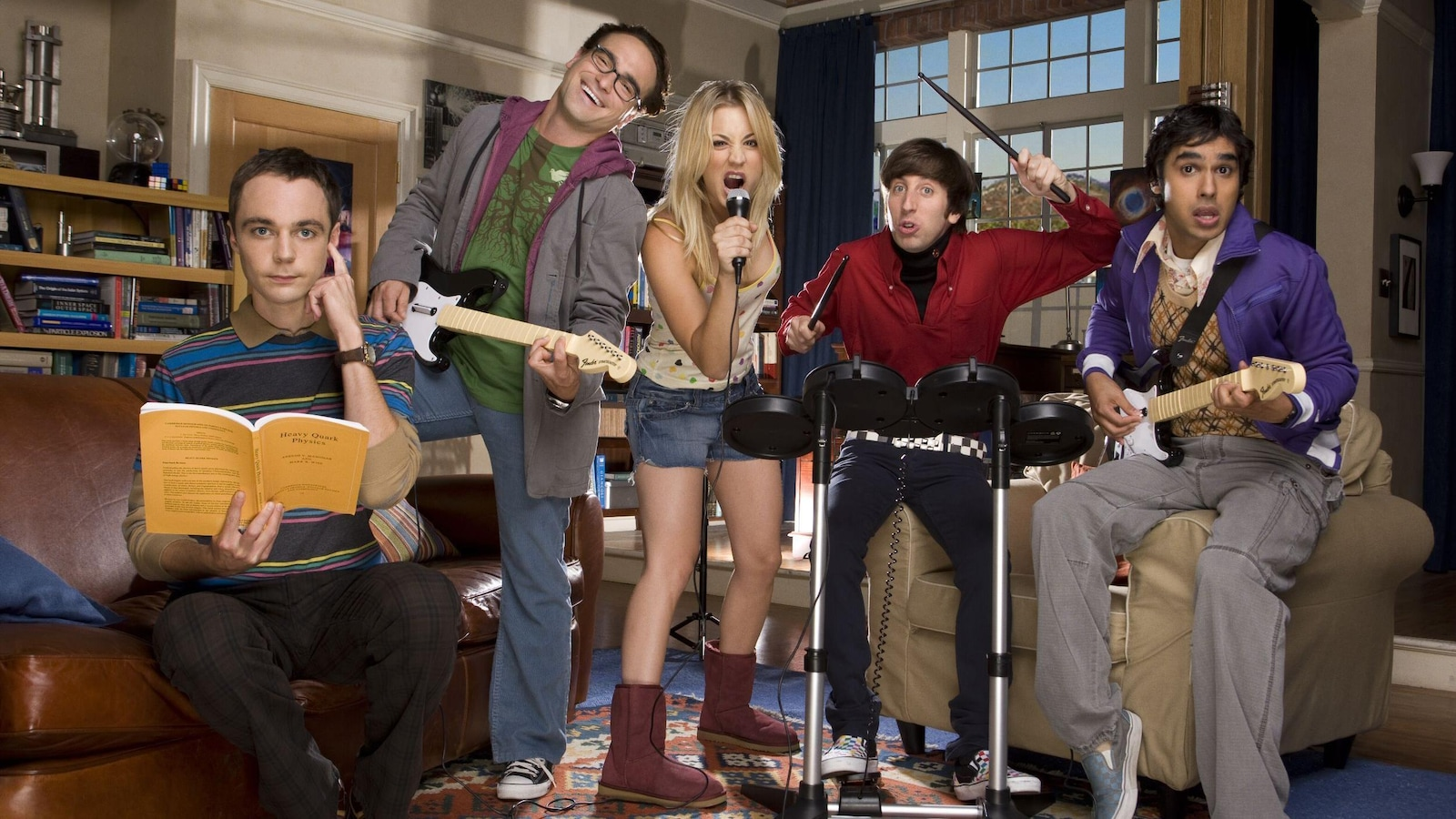 Quatre personnes jouent de la musique pendant que Sheldon essaie de lire en se bouchant une oreille.