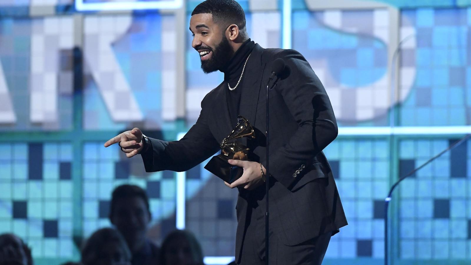Drake tient un trophée en forme de gramophone dans ses mains.