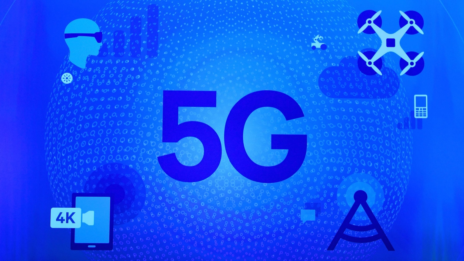 Un pictogramme à l'effigie du 5G : on y voit un individu qui porte des lunettes de réalité virtuelle, un drone, un téléphone dont l'écran affiche une résolution 4K et une tour de téléphonie cellulaire.