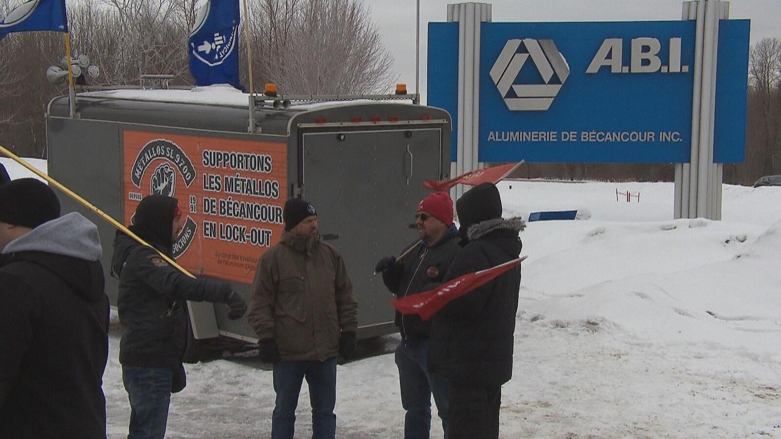 Pancarte de l'ABI derrière des travailleurs qui tiennent des pancartes