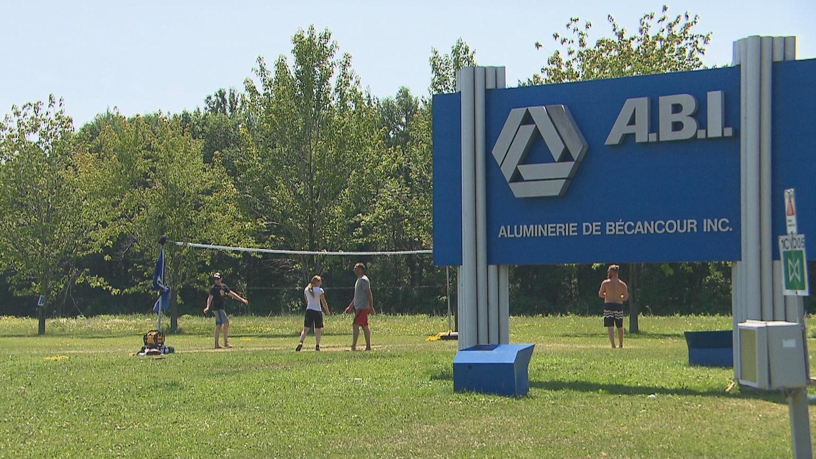 Les syndiqués jouent au volleyball sur le gazon du terrain de l'ABI, à Bécancour, près de l'affiche extérieure