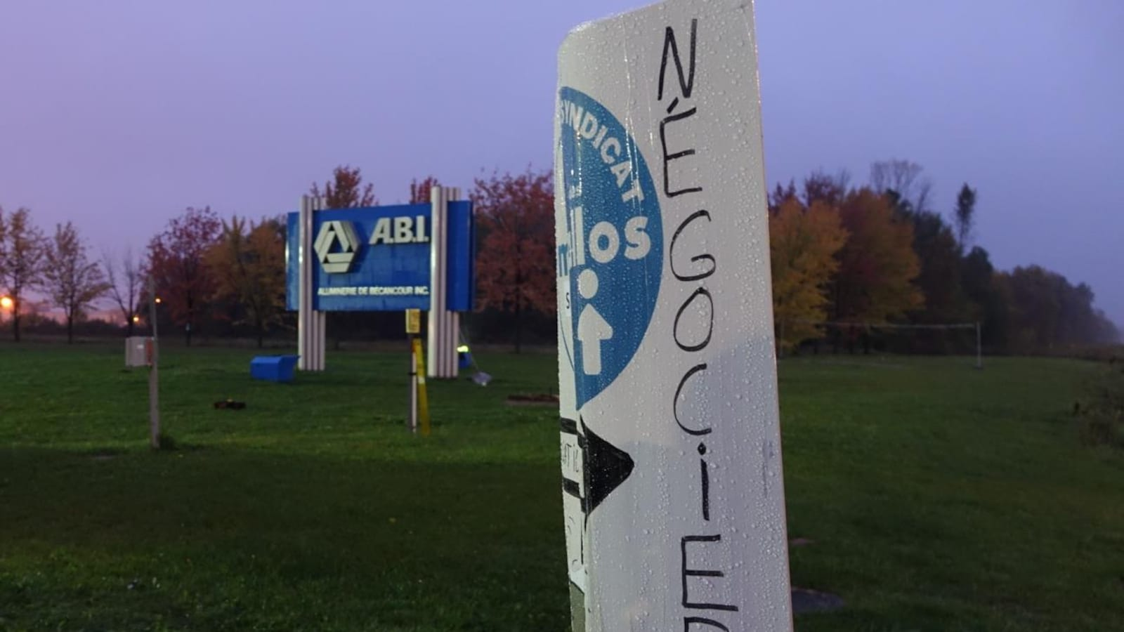 Une pancarte du syndicat des Métallos devant la pancarte qui se trouve à l'entrée du site de l'ABI