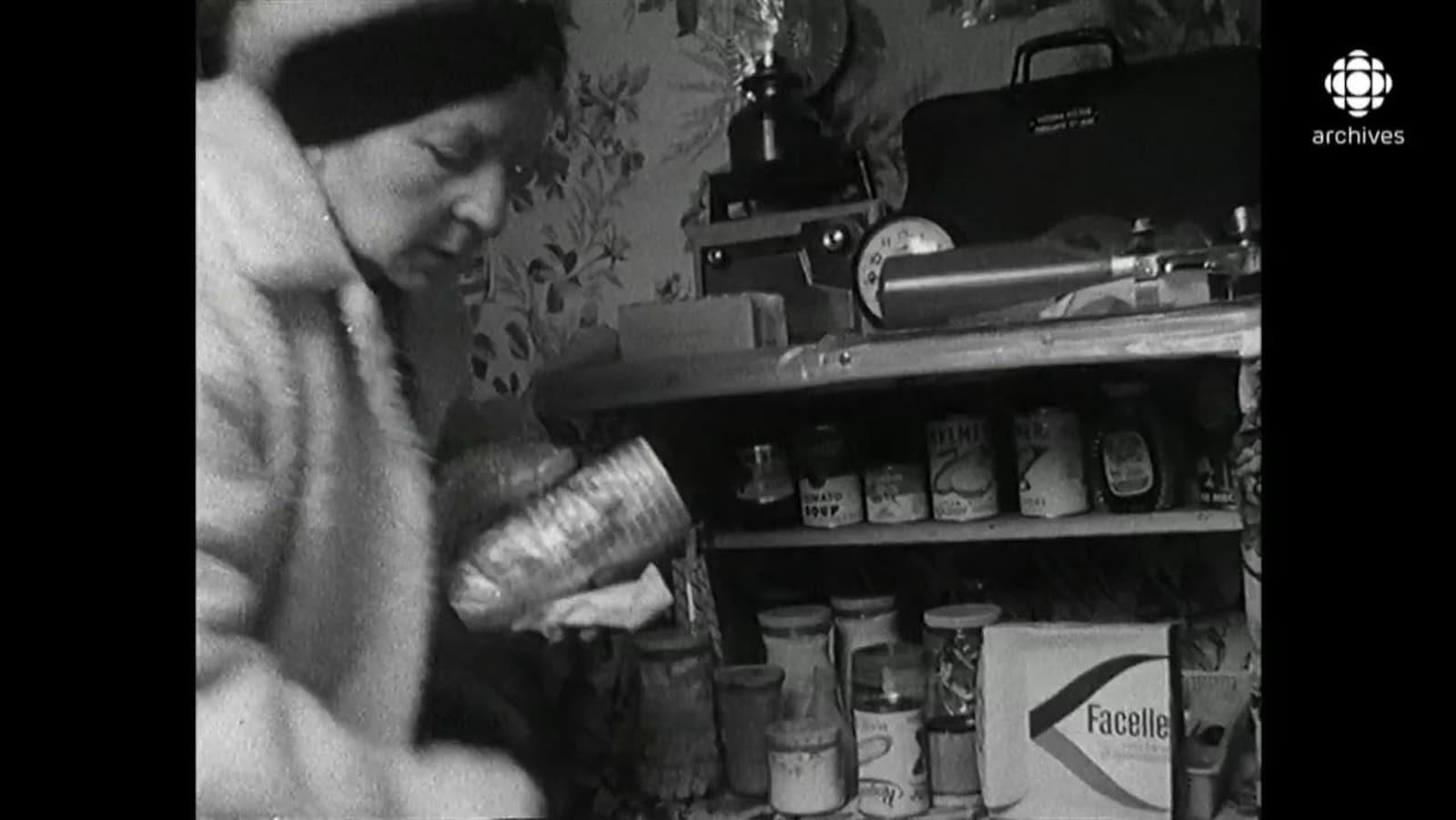Femme chaudement habillée remplissant les tablettes de conserves de son abri antinucléaire