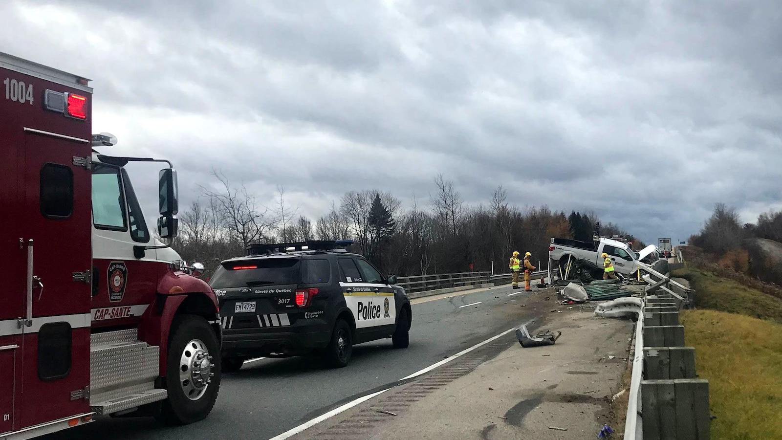Photo de la scène d'accident. On aperçoit une camionnette blanche accidentée. Un véhicule utilitaire sport de la Sûreté du Québec et un camion de pompier.
