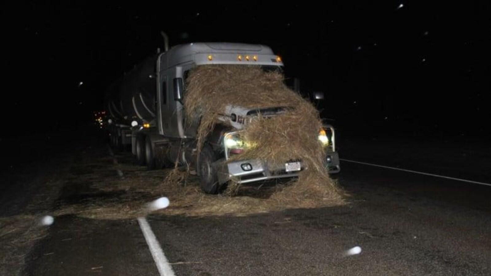 Un ballot de paille écrasé sur le devant d'un camion semi-remorque arrêté sur une autoroute.